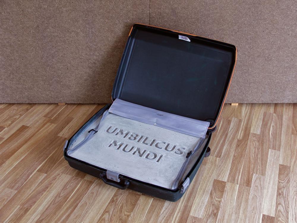 UMBILICUS MUNDI . Objekt (2014) Material: Schalenkoffer mit Rollen, Schriftzug, Beton. Grösse: 68x54x24cm.